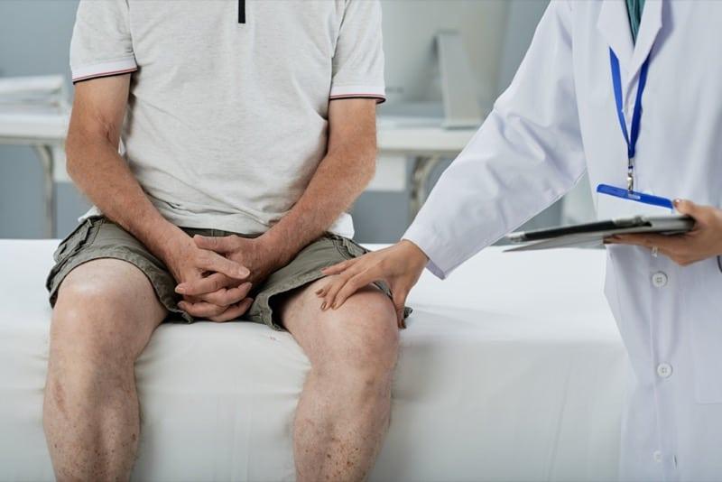 doctor examining burning legs symptoms